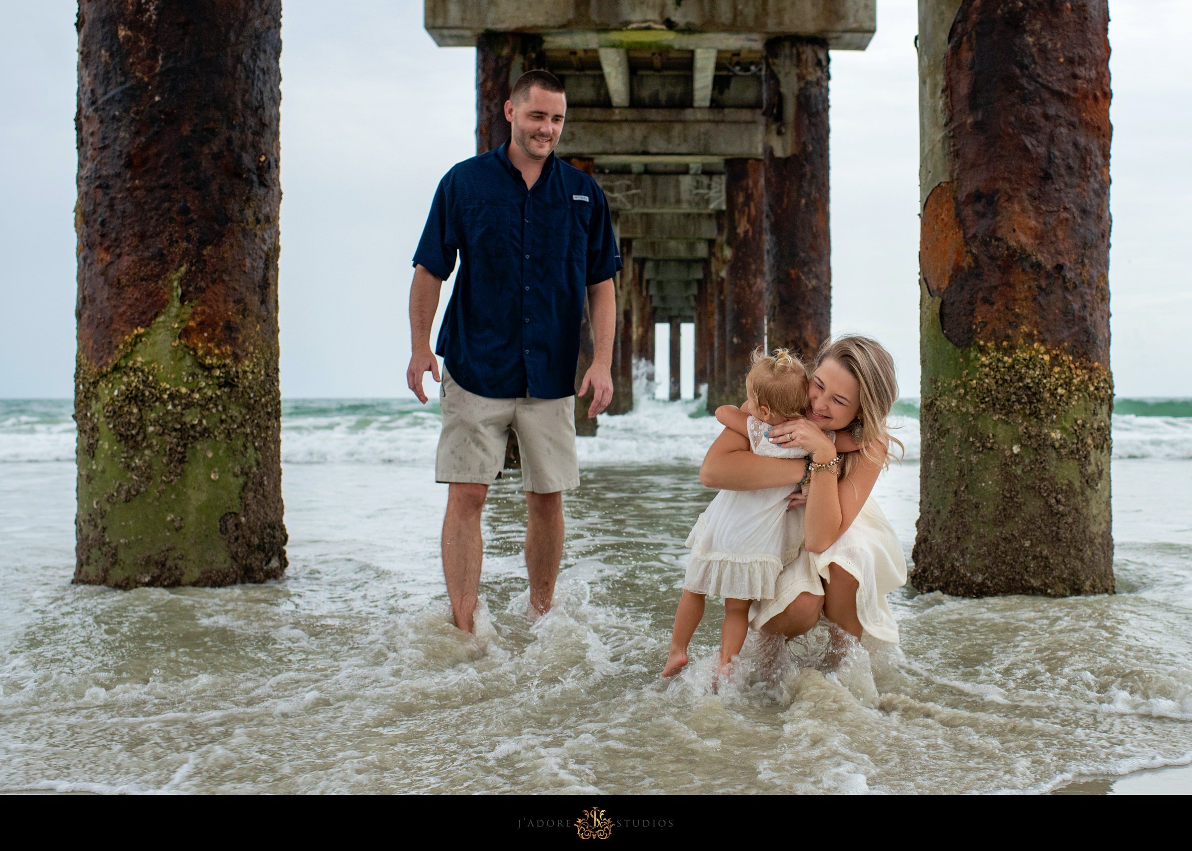 Mother and daughter hugging as father watches under the pier in Saint Augustine Florida
