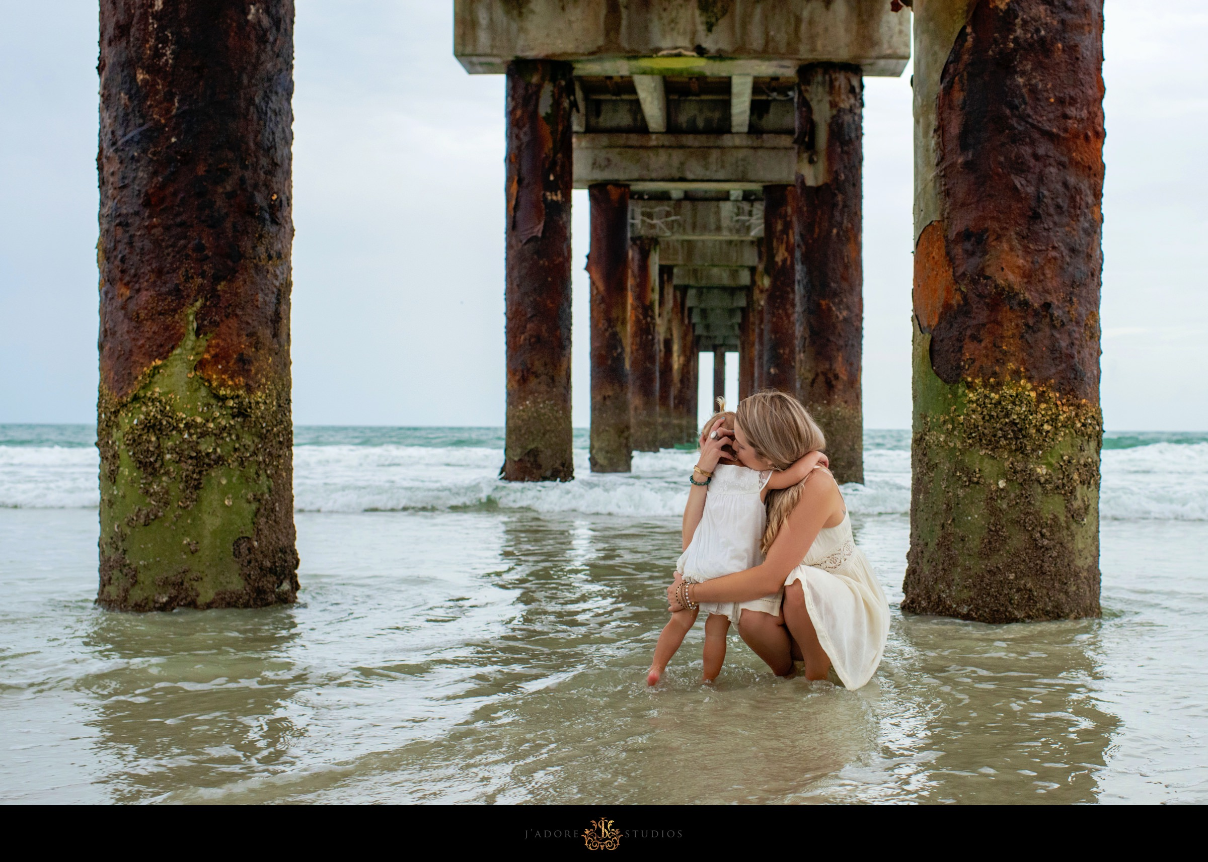 Mother and daughter hugging under the pier in Saint Augustine Florida
