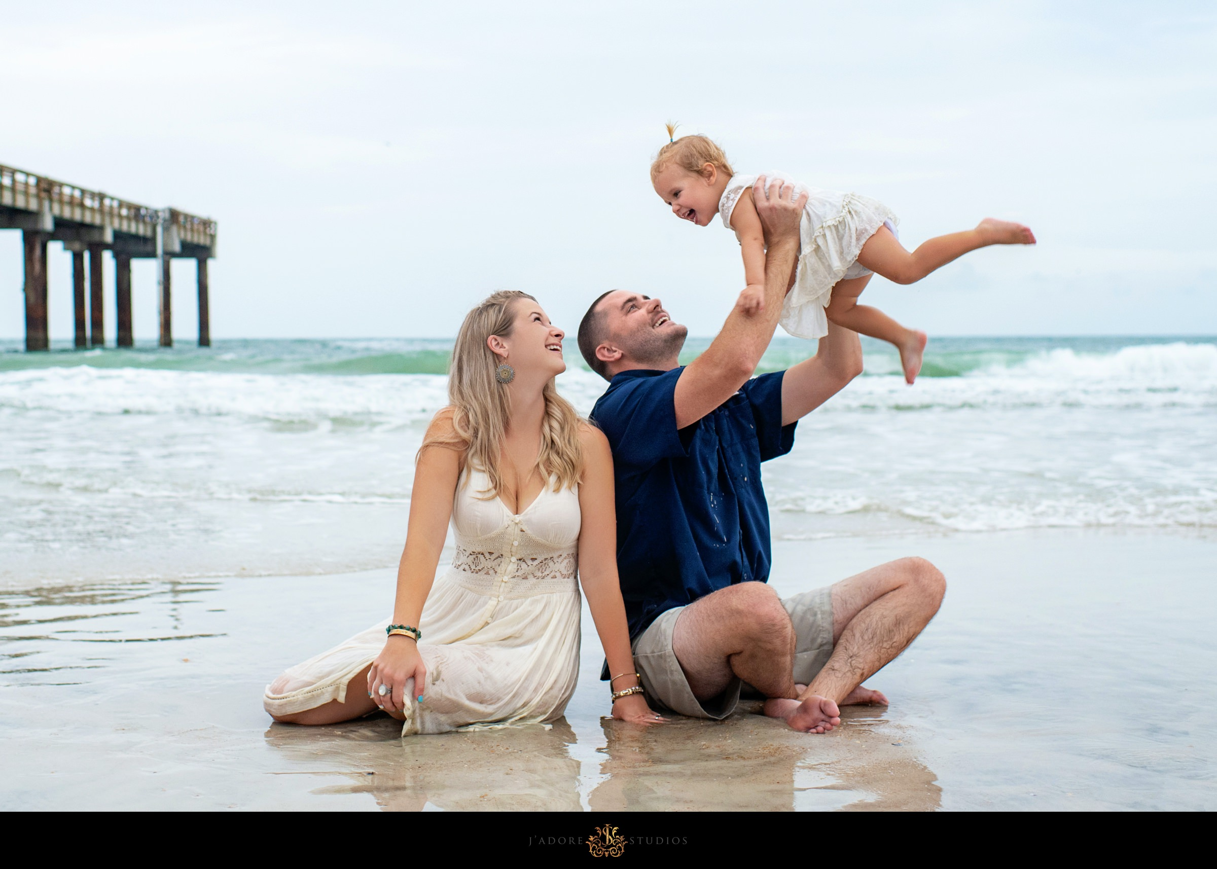 Family sitting on the beach playing with daughter in Saint Augustine Florida